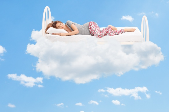 Woman sleeping on a comfortable bed in the clouds
