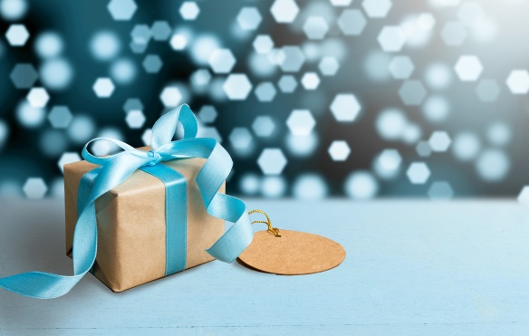 Christmas gift or New Year with blue ribbon and greeting card on wood table on bokeh background. Tiny and Handmade gift box concept.