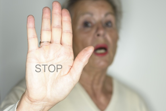 senior woman with her hands signaling to stop over light background