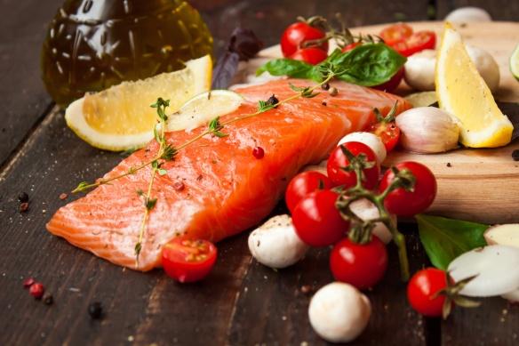 свежая рыба с овощами на деревянном столе