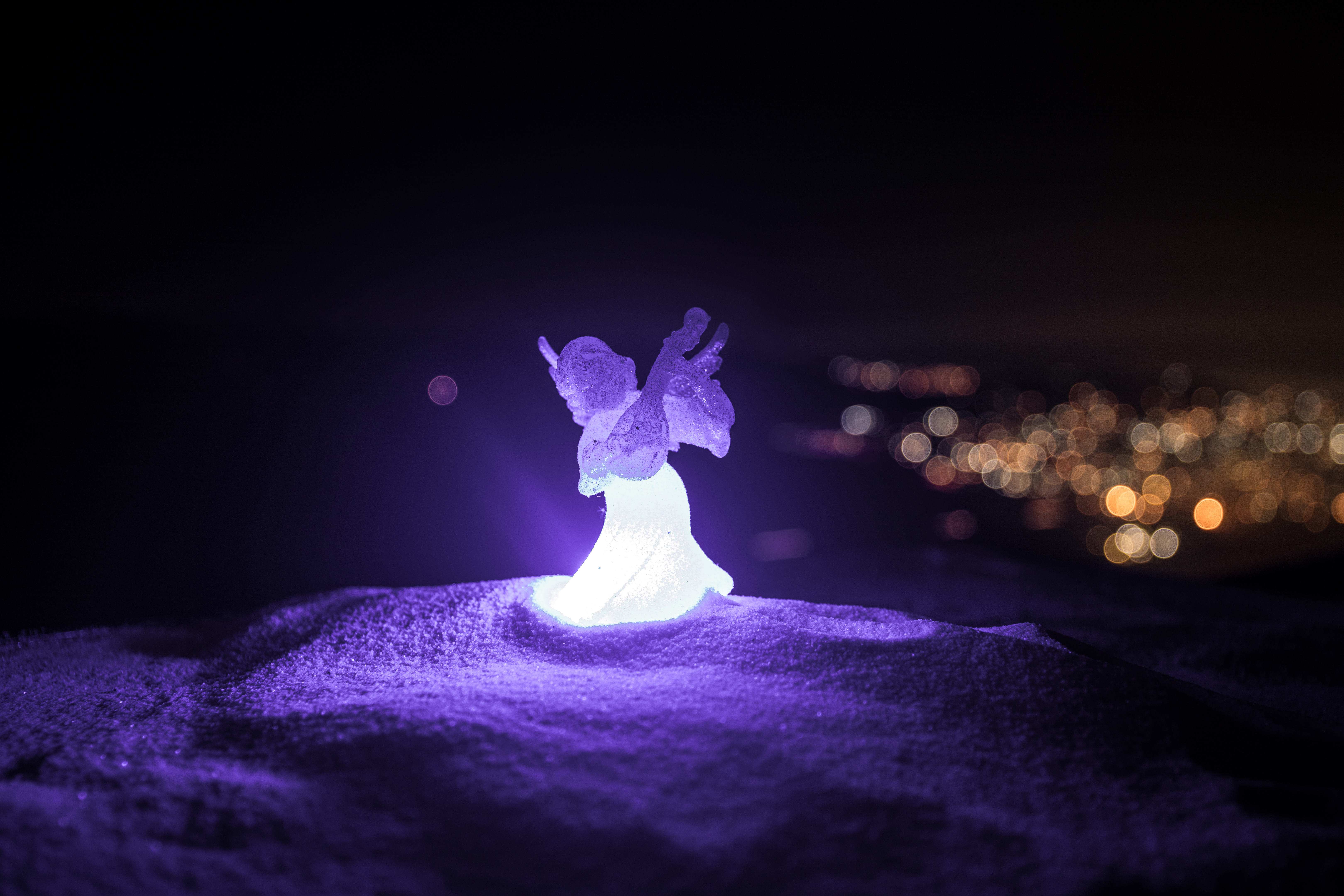 christmas angel on blur bokeh city lights at night on background. Little white guardian angel in snow.