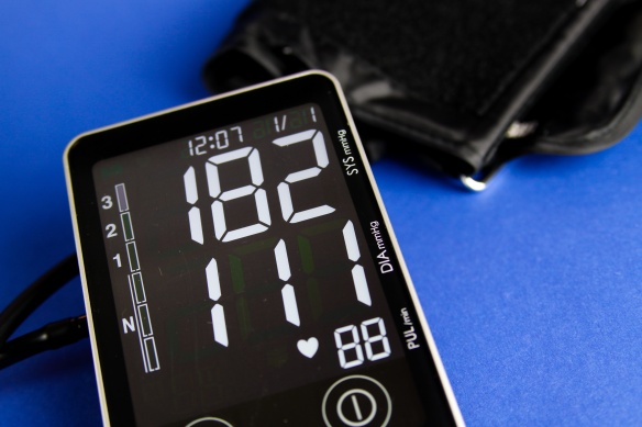 Close up of digital monitor device with cuff showing high diastolic and systolic blood pressure