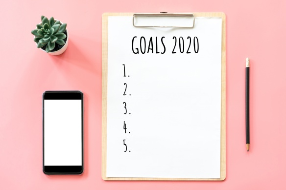 2020 New year concept. Goals list in stationery, blank clipboard, smartphone, pot plant on pink pastel color with copy space