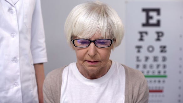 Depressed old woman in eyeglasses on ophthalmologist appointment, vision problem